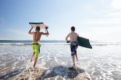 Adolescentes que practican surf Imágenes de archivo libres de regalías