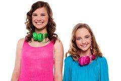 Adolescentes que presentan con los auriculares alrededor de cuello Fotografía de archivo