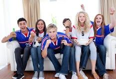 Adolescentes que prestam atenção a um fósforo de futebol Fotografia de Stock