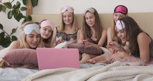 Adolescentes que riem ao olhar o índice em linha dos meios vídeos de arquivo