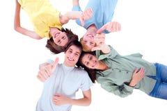 Adolescentes que se acuestan con los pulgares para arriba Fotografía de archivo
