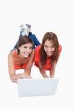 Adolescentes que se acuestan detrás de una computadora portátil Imágenes de archivo libres de regalías