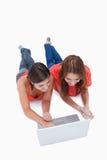 Adolescentes que se acuestan mientras que mira una computadora portátil Imagen de archivo