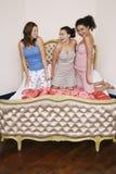 Adolescentes que se arrodillan en cama enrrollada Foto de archivo libre de regalías