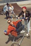 Adolescentes que se divierten con el carro de la compra en parque del monopatín Fotografía de archivo