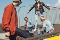 Adolescentes que se divierten con el carro de la compra en parque del monopatín Fotos de archivo