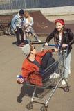 Adolescentes que se divierten con el carro de la compra en parque del monopatín Fotografía de archivo libre de regalías