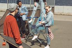 Adolescentes que se divierten con el carro de la compra en parque del monopatín Imágenes de archivo libres de regalías
