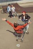 Adolescentes que se divierten con el carro de la compra en parque del monopatín Imagen de archivo libre de regalías