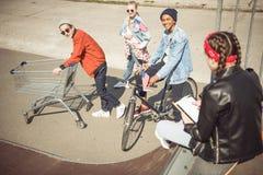 Adolescentes que se divierten con el carro de la compra y la bicicleta en parque del monopatín Imagen de archivo libre de regalías