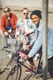 Adolescentes que se divierten con el carro de la compra y la bicicleta en parque del monopatín Foto de archivo libre de regalías