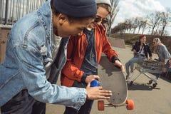 Adolescentes que se divierten con el patín en parque del monopatín Fotos de archivo