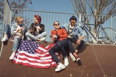 Adolescentes que se divierten con la bandera americana en parque del monopatín Imágenes de archivo libres de regalías