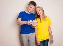 Adolescentes que se divierten con los tel?fonos m?viles Forma de vida y concepto modernos de la tecnolog?a Ni?os que miran la fot foto de archivo
