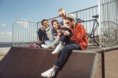 Adolescentes que se divierten con smartphone en parque del monopatín Foto de archivo libre de regalías