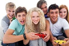 Adolescentes que se divierten el jugar de los juegos video Imágenes de archivo libres de regalías