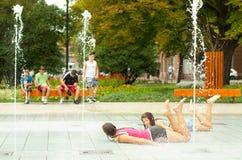 Adolescentes que se divierten en la fuente de las ciudades Imagenes de archivo