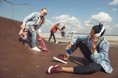Adolescentes que se divierten en parque del monopatín Imagenes de archivo