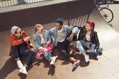 Adolescentes que se divierten en parque del monopatín con el tablero del penique Imagenes de archivo