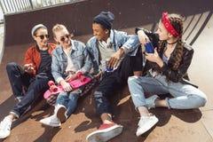 Adolescentes que se divierten en parque del monopatín con el tablero del penique Fotos de archivo libres de regalías