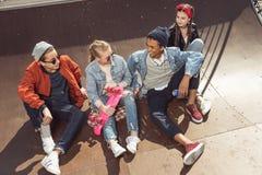 Adolescentes que se divierten en parque del monopatín con el tablero del penique Fotos de archivo