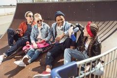 Adolescentes que se divierten en parque del monopatín con el tablero del penique Fotografía de archivo libre de regalías
