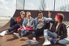 Adolescentes que se divierten en parque del monopatín con el tablero del penique Foto de archivo libre de regalías