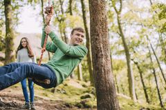 Adolescentes que se divierten en un oscilación de la cuerda Imagenes de archivo