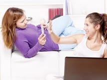 Adolescentes que se divierten usando los adminículos electrónicos Imagen de archivo libre de regalías