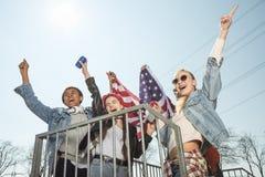 Adolescentes que se divierten y que agitan la bandera americana en parque del monopatín Imágenes de archivo libres de regalías
