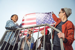 Adolescentes que se divierten y que agitan la bandera americana en parque del monopatín Imagen de archivo