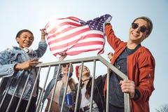 Adolescentes que se divierten y que agitan la bandera americana en parque del monopatín Fotografía de archivo
