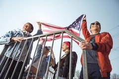 Adolescentes que se divierten y que agitan la bandera americana en parque del monopatín Imagenes de archivo