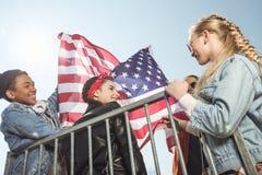 Adolescentes que se divierten y que agitan la bandera americana en parque del monopatín Fotografía de archivo libre de regalías