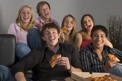 Adolescentes que se divierten y que comen la pizza Imágenes de archivo libres de regalías