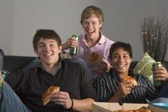 Adolescentes que se divierten y que comen la pizza Foto de archivo
