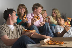 Adolescentes que se divierten y que comen la pizza Fotografía de archivo libre de regalías