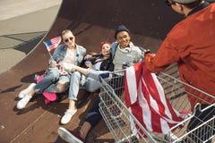 Adolescentes que se divierten y que mienten con la bandera americana en parque del monopatín Imagen de archivo