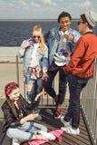 Adolescentes que se divierten y que presentan en parque del monopatín con el tablero del penique Fotografía de archivo