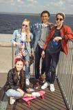 Adolescentes que se divierten y que presentan en parque del monopatín con el tablero del penique Imágenes de archivo libres de regalías
