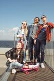 Adolescentes que se divierten y que presentan en parque del monopatín con el tablero del penique Imagen de archivo