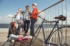 Adolescentes que se divierten y que presentan en parque del monopatín con el tablero y la bicicleta del penique Fotografía de archivo
