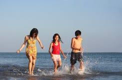 Adolescentes que se ejecutan a lo largo de la playa Fotografía de archivo libre de regalías