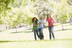 Adolescentes que se ejecutan a través de parque Foto de archivo