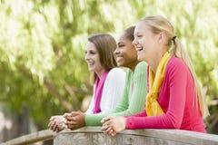 Adolescentes que se inclinan en el pasamano de madera Imagenes de archivo