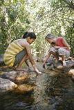 Adolescentes que se ponen en cuclillas en piedra por la corriente Imagen de archivo libre de regalías