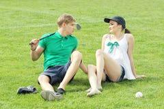 Adolescentes que se relajan en un campo de hierba verde Imagen de archivo