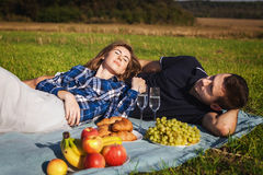 Adolescentes que se relajan en una comida campestre manzanas, uvas, cruasanes Fotografía de archivo libre de regalías