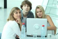 Adolescentes que se sientan alrededor de una computadora portátil Fotos de archivo