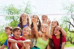 Adolescentes que se sientan bajo señalar neto del voleibol Imagenes de archivo